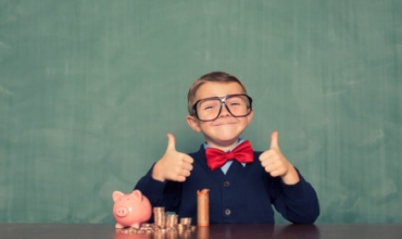 kid with piggy bank giving two thumbs up